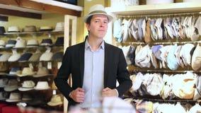 El hombre adulto feliz intenta encendido al ecuatoriano Panamá en la tienda del sombrero almacen de metraje de vídeo