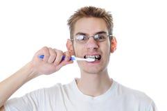 El hombre adulto joven aplica los dientes con brocha Fotografía de archivo libre de regalías