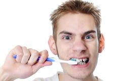 El hombre adulto joven aplica los dientes con brocha Foto de archivo libre de regalías