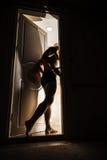 El hombre adulto joven entra en la puerta abierta de oscuridad Foto de archivo libre de regalías
