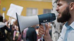 El hombre adulto joven grita en megáfono Él grita violentamente y cámara lenta enojada almacen de metraje de vídeo