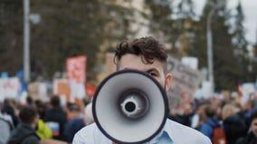 El hombre adulto joven grita en megáfono Él grita violentamente y cámara lenta enojada metrajes