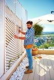 El hombre adulto joven que construye la pared de madera de la pérgola en patio del tejado divide en zonas en casa Foto de archivo
