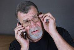 El hombre adulto pensativo escucha en el teléfono móvil Imagenes de archivo