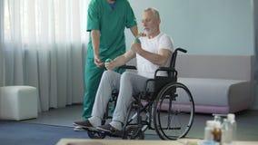El hombre adulto que levanta apenas las pesas de gimnasia que estiran el brazo débil muscles, programa de la recuperación almacen de metraje de vídeo