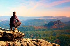 El hombre adulto que sube en la cima de la roca con la vista aérea hermosa del valle brumoso profundo grita Fotos de archivo