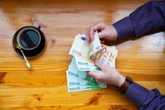 El hombre adulto rico cuenta el dinero y el café euro de la bebida Fotos de archivo