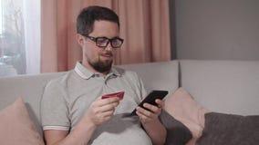 El hombre adulto se está sentando en el sofá en hogar y está poniendo datos de la tarjeta en el smartphone app almacen de metraje de vídeo
