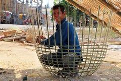 El hombre adulto sonriente en una camisa azul y vaqueros está haciendo la cesta laosiana tradicional en la calle de la ciudad Fotografía de archivo