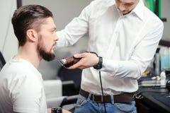 El hombre afeita su barba con podadoras de pelo Imagenes de archivo