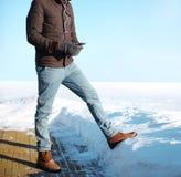 El hombre africano de la moda del invierno escucha la música en un smartphone Foto de archivo libre de regalías