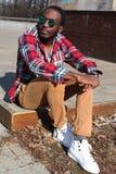 El hombre africano del retrato de la moda con los auriculares escucha la música Imagenes de archivo