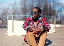 El hombre africano del retrato de la moda con los auriculares escucha la música en ciudad Foto de archivo libre de regalías