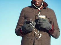 El hombre africano escucha la música usando el smartphone que sostiene la taza de café sobre fondo del cielo azul Imagen de archivo libre de regalías