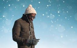 El hombre africano joven de la moda escucha la música en smartphone en día de invierno Foto de archivo