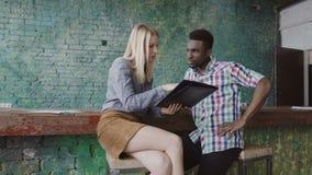 El hombre africano joven y la mujer caucásica se sienta cerca del contador de la barra en la oficina moderna y la discusión de lo metrajes