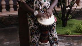 El hombre africano juega los tambores africanos