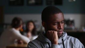 El hombre africano trastornado siente solo excluido rechazado por los amigos blancos almacen de metraje de vídeo