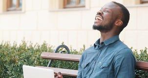 El hombre afroamericano atractivo que trabaja en el ordenador portátil se sienta en el banco Buenas noticias recibidas emocionada