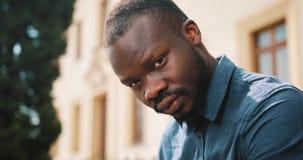 El hombre afroamericano cansado se sienta en el banco afuera Un hombre triste, frustrado, dice no almacen de video