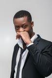 El hombre afroamericano cierra la boca por la mano izquierda imagen de archivo libre de regalías
