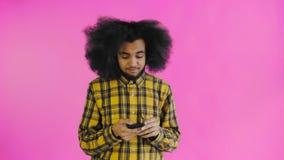El hombre afroamericano con el pelo rizado está pensando antes envía el mensaje en fondo púrpura Concepto de emociones almacen de video