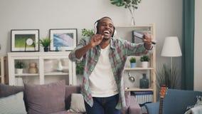 El hombre afroamericano creativo está cantando en escuchar teledirigido y de baile la música en los auriculares que se relajan en almacen de metraje de vídeo