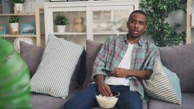 El hombre afroamericano emocional está mirando la novela de suspense en la TV en casa y está comiendo las palomitas que se sienta metrajes