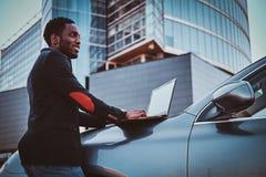 El hombre afroamericano está trabajando en su ordenador portátil afuera imágenes de archivo libres de regalías