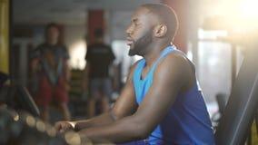El hombre afroamericano hermoso cansó después del entrenamiento activo en gimnasio, forma de vida almacen de metraje de vídeo