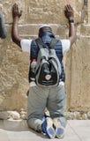 El hombre afroamericano indefinido ruega en la pared occidental fotos de archivo