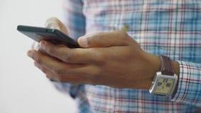 El hombre afroamericano joven está sosteniendo smartphone disponible, situación en oficina ligera metrajes