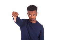 El hombre afroamericano joven infeliz que hace los pulgares abajo gesticula es Imagen de archivo