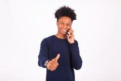 El hombre afroamericano joven que lleva a cabo smartphonemaking manosea con los dedos para arriba Foto de archivo libre de regalías