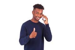 El hombre afroamericano joven que lleva a cabo smartphonemaking manosea con los dedos para arriba Fotos de archivo