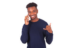 El hombre afroamericano joven que lleva a cabo smartphonemaking manosea con los dedos para arriba Imagenes de archivo