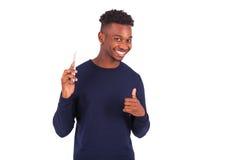 El hombre afroamericano joven que lleva a cabo smartphonemaking manosea con los dedos para arriba Fotos de archivo libres de regalías