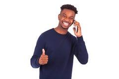 El hombre afroamericano joven que lleva a cabo smartphonemaking manosea con los dedos para arriba Imagen de archivo libre de regalías