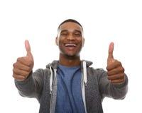 El hombre afroamericano joven que sonríe con los pulgares sube la muestra Foto de archivo