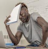 El hombre afroamericano negro desesperado y abrumado joven del estudiante en el trabajo de la tensión en casa subrayado con el or Imágenes de archivo libres de regalías