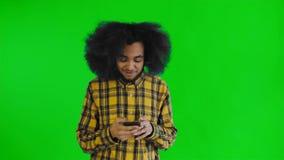 El hombre afroamericano recibió un nuevo mensaje en su teléfono en la pantalla verde o el fondo dominante de la croma Concepto de almacen de metraje de vídeo