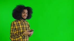 El hombre afroamericano recibi? un nuevo mensaje en su tel?fono en la pantalla verde o el fondo dominante de la croma Concepto de almacen de metraje de vídeo