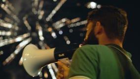 El hombre agita en el fondo del fuego artificial Un hombre enojado da el megáfono fuerte del discurso almacen de metraje de vídeo