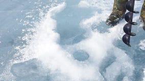 El hombre agujerea los tornillos del hielo del hielo metrajes