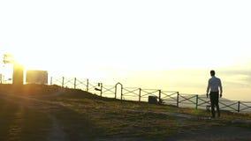El hombre aislado está caminando a lo largo de la trayectoria en el fondo del cielo colorido durante la puesta del sol en el camp almacen de metraje de vídeo
