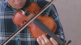 El hombre ajusta el violín que tuerce los pernos y que los juega con un arco almacen de metraje de vídeo
