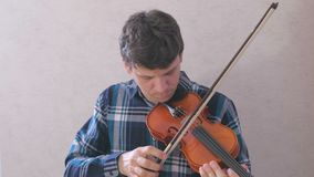 El hombre ajusta el violín que tuerce los pernos y que los juega con un arco almacen de video
