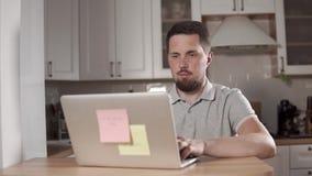 El hombre alegre adulto está trabajando con el cuaderno en un hogar, sentándose en una cocina almacen de metraje de vídeo
