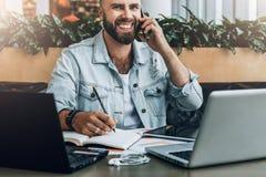 El hombre alegre barbudo joven se sienta en la tabla delante de los ordenadores portátiles, hablando en el teléfono móvil mientra imagen de archivo libre de regalías