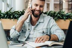 El hombre alegre barbudo se está sentando en la tabla delante de los ordenadores portátiles, hablando en el teléfono El Freelance imágenes de archivo libres de regalías